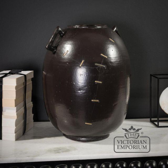 Broken and repaired black vase