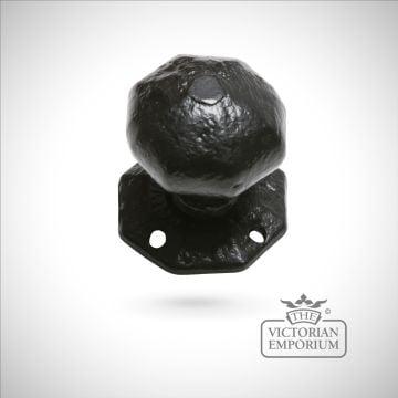 Black iron handcrafted door knob on hexagonal plate