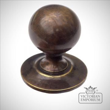 Round cabinet knob in antique brass